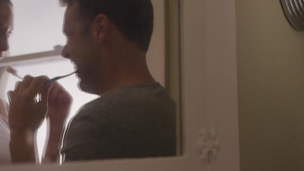 Handheld shot of playful couple reflecting on mirror while brushing teeth in bathroom Royalty-free stock video
