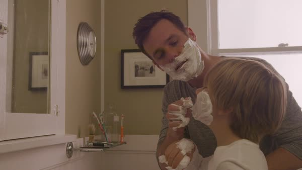 Handheld shot of happy father assisting son in applying shaving cream on face at bathroom Royalty-free stock video