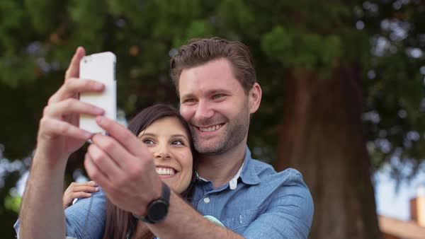 Tilt up shot of happy couple taking selfie at park Royalty-free stock video