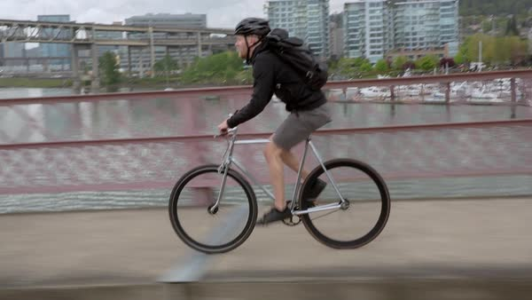 Handheld shot of male commuter riding bicycle on bridge over river in city against cloudy sky Royalty-free stock video