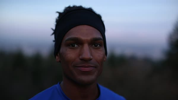 Handheld close-up portrait of happy athlete against sky at dusk Royalty-free stock video