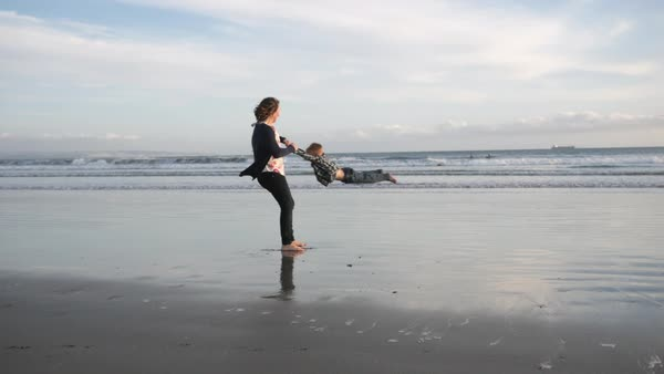 Handheld shot of mother playing with son on shore at beach against sky Royalty-free stock video