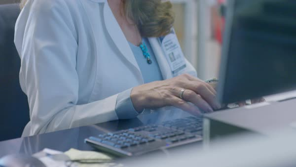 Tilt shot of female doctor using desktop computer in laboratory seen through glass window Royalty-free stock video