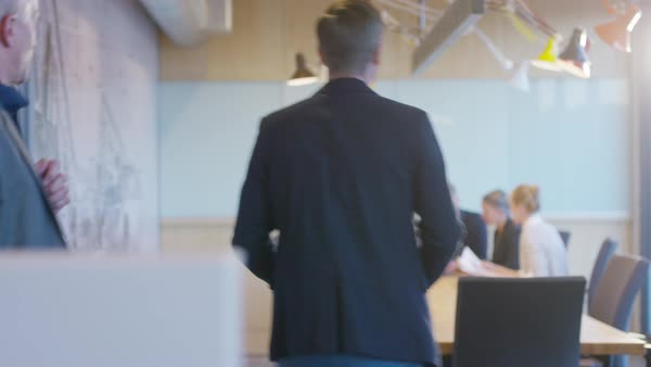 Handheld shot of businessman explaining to colleagues while writing on whiteboard in meeting Royalty-free stock video