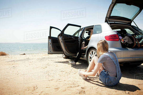 Young woman sitting next to car and tying shoes on beach Royalty-free stock photo