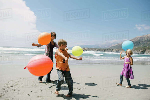 Happy family playing with balloons while standing on sand at beach Royalty-free stock photo