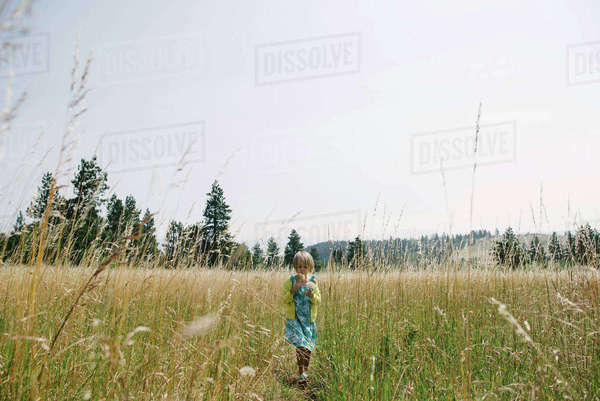 Girl walking on grassy field against clear sky Royalty-free stock photo