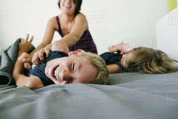 Happy mother playing with children on bed Royalty-free stock photo