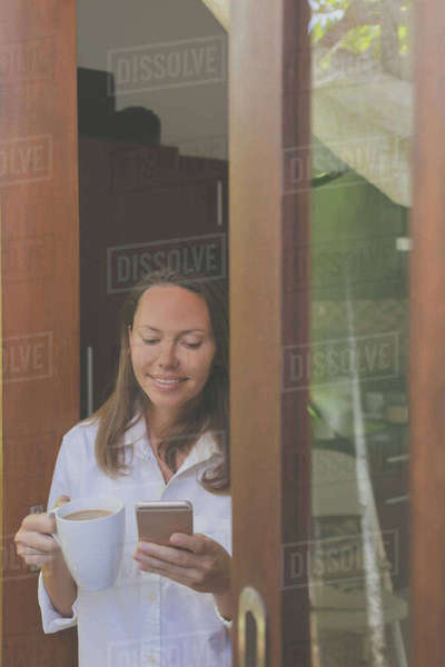 Woman with coffee cup using smart phone while standing by window at home Royalty-free stock photo