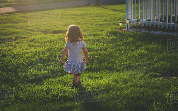 Rear view of girl walking on grassy field at yard during sunset Royalty-free stock photo
