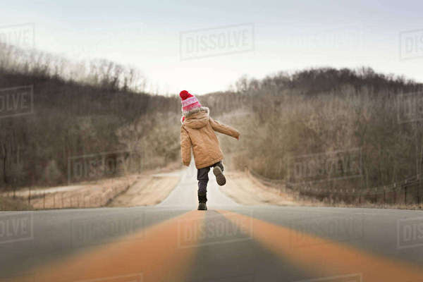 Full length rear view of boy walking on country road Royalty-free stock photo
