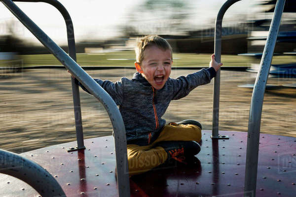 Portrait of cheerful boy sitting on merry-go-round Royalty-free stock photo