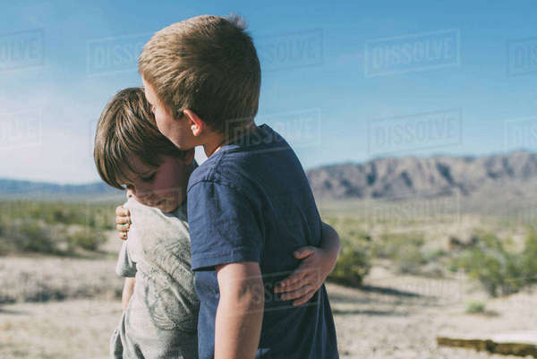 Boy kissing brother while standing at Joshua Tree National Park against sky during sunny day Royalty-free stock photo