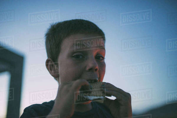 Close-up portrait of boy eating smore against sky at Joshua Tree National Park Royalty-free stock photo