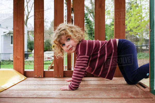 Side view portrait of girl kneeling on wooden outdoor play equipment at yard Royalty-free stock photo