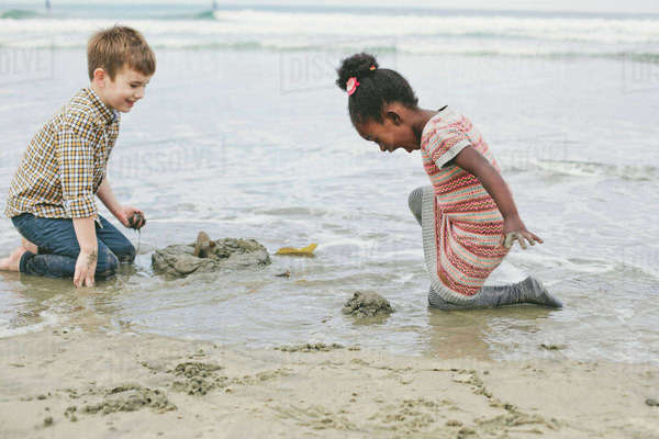 Brother and sister playing with sand at beach Royalty-free stock photo