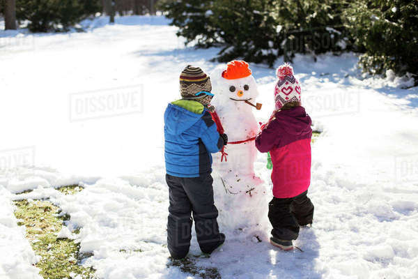 Rear view of siblings making snowman while standing on snow covered field Royalty-free stock photo