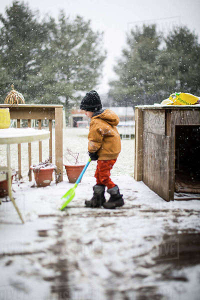 Side view of boy removing snow with shovel at yard Royalty-free stock photo
