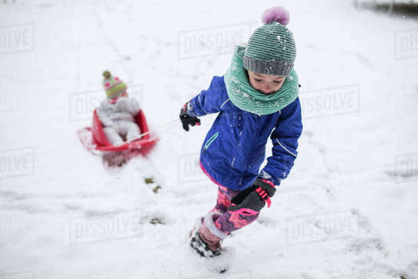 Girl pulling sister sitting in sled on snow covered field Royalty-free stock photo