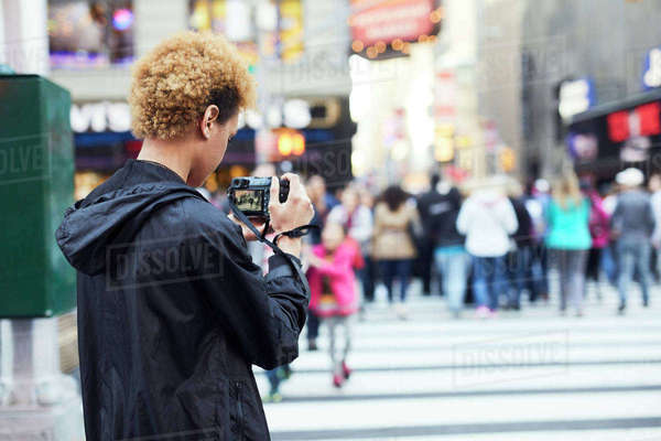 Rear view of young woman photographing on city street Royalty-free stock photo
