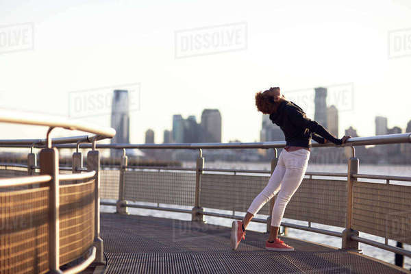 Young woman exercising on footpath by river in city against clear sky Royalty-free stock photo