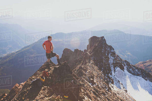 Rear view of man with hands on hip looking at view while standing on mountain against sky Royalty-free stock photo