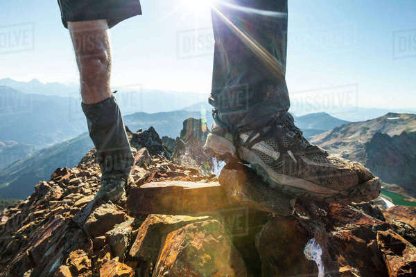 Low section of man standing on rocky mountain Royalty-free stock photo