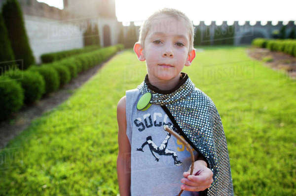 Portrait of boy wearing cape and holding stick while standing on grassy field at park Royalty-free stock photo