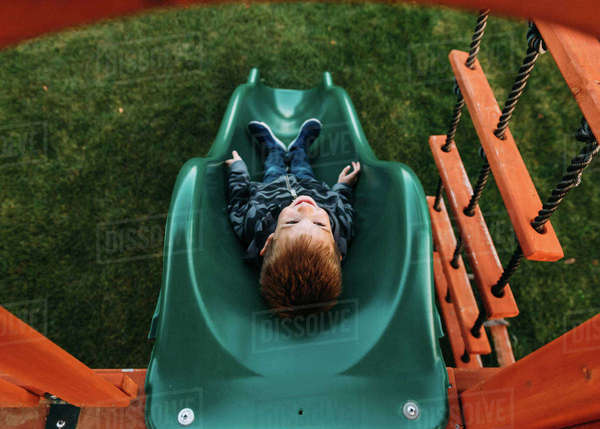 High angle view of happy boy sliding at park Royalty-free stock photo