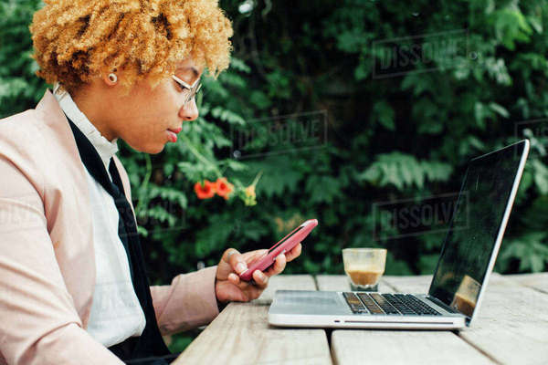 Side view of woman using smart phone while sitting at park Royalty-free stock photo