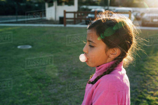 Side view of girl blowing bubble gum at park Royalty-free stock photo