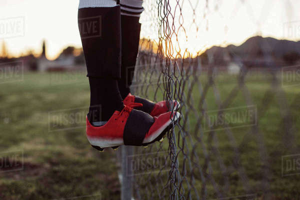 Low section of girl climbing chainlink fence at playground Royalty-free stock photo