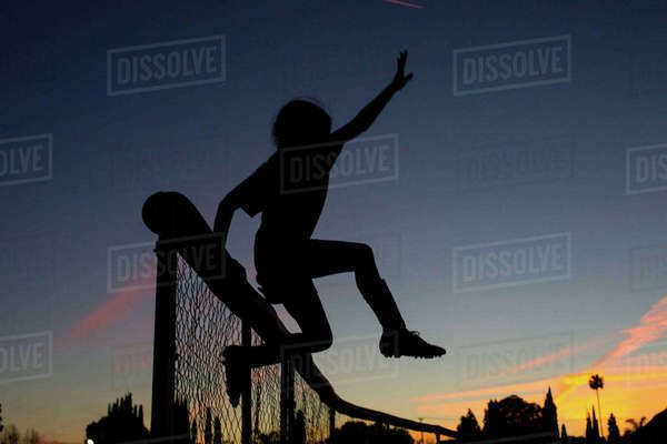 Silhouette sporty girl jumping over fence during dusk against sky Royalty-free stock photo
