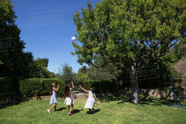 Female friends playing with balloon at yard Royalty-free stock photo
