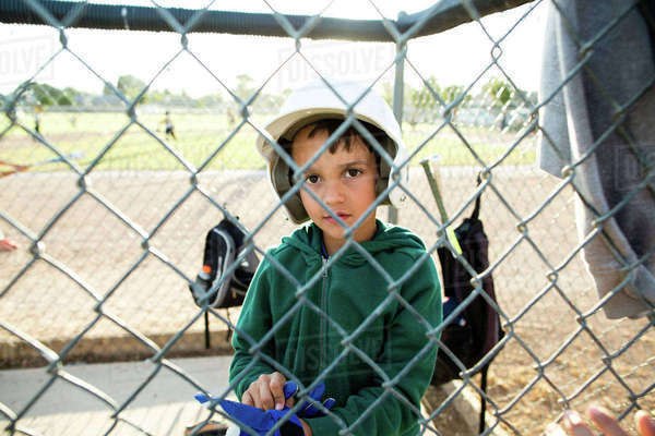Portrait of boy wearing baseball helmet while sitting in dugout seen through chainlink fence Royalty-free stock photo