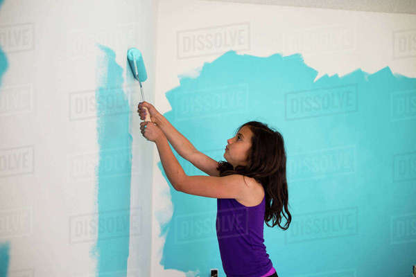 Side view of girl painting wall with paint roller at home Royalty-free stock photo