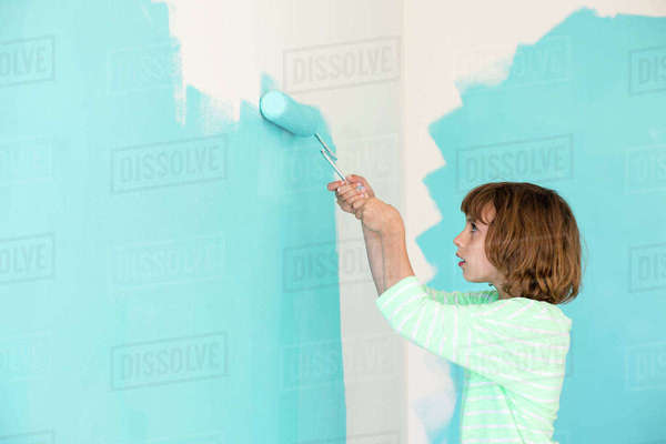 Side view of girl painting wall at home Royalty-free stock photo