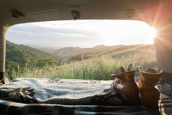 Hiking boots and blanket in sports utility vehicle with hills in background Royalty-free stock photo