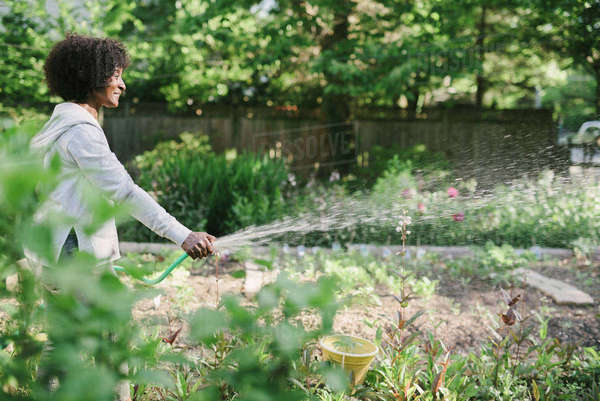 Side view of mature woman watering plants in garden Royalty-free stock photo