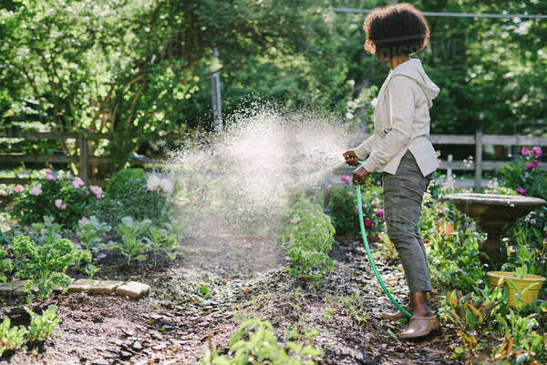Side view of mature woman watering plants in yard Royalty-free stock photo