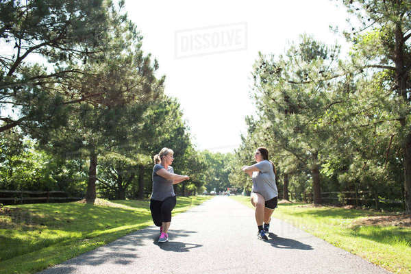 Mother and daughter stretching arms and legs on footpath at park during sunny day Royalty-free stock photo