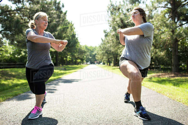 Mother and daughter exercising on footpath at park during sunny day Royalty-free stock photo