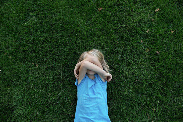 Overhead view of girl covering face while lying on grassy field Royalty-free stock photo
