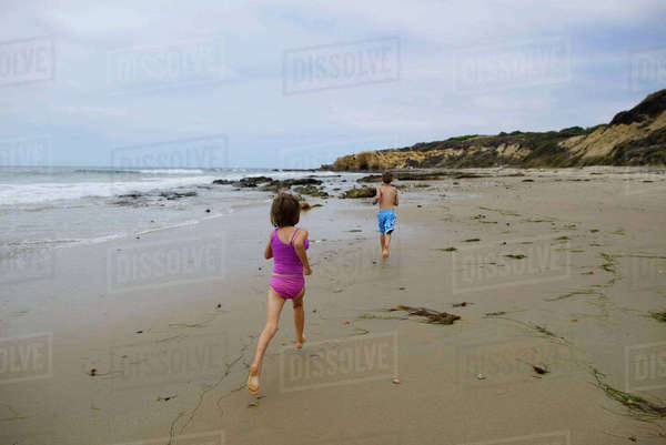 Rear view of siblings running on beach against sky at Crystal Cove State Park Royalty-free stock photo