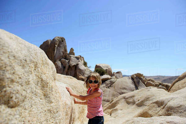Portrait of girl standing by rocks at Joshua Tree National Park against clear sky during sunny day Royalty-free stock photo