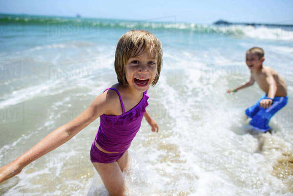 Portrait of happy girl playing with brother in sea at Oceanside beach Royalty-free stock photo