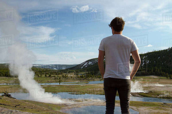 Rear view of hiker looking at steam coming out from hot springs at Yellowstone National Park against sky Royalty-free stock photo
