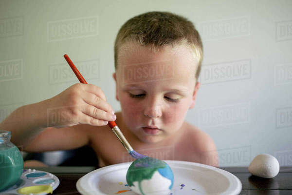 Shirtless boy coloring Easter egg while sitting by table at home Royalty-free stock photo
