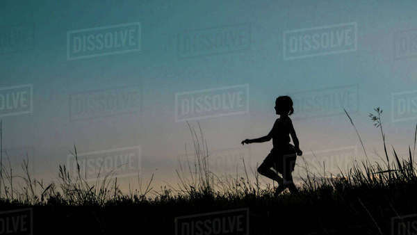 Silhouette girl walking on grassy field against clear sky during dusk Royalty-free stock photo