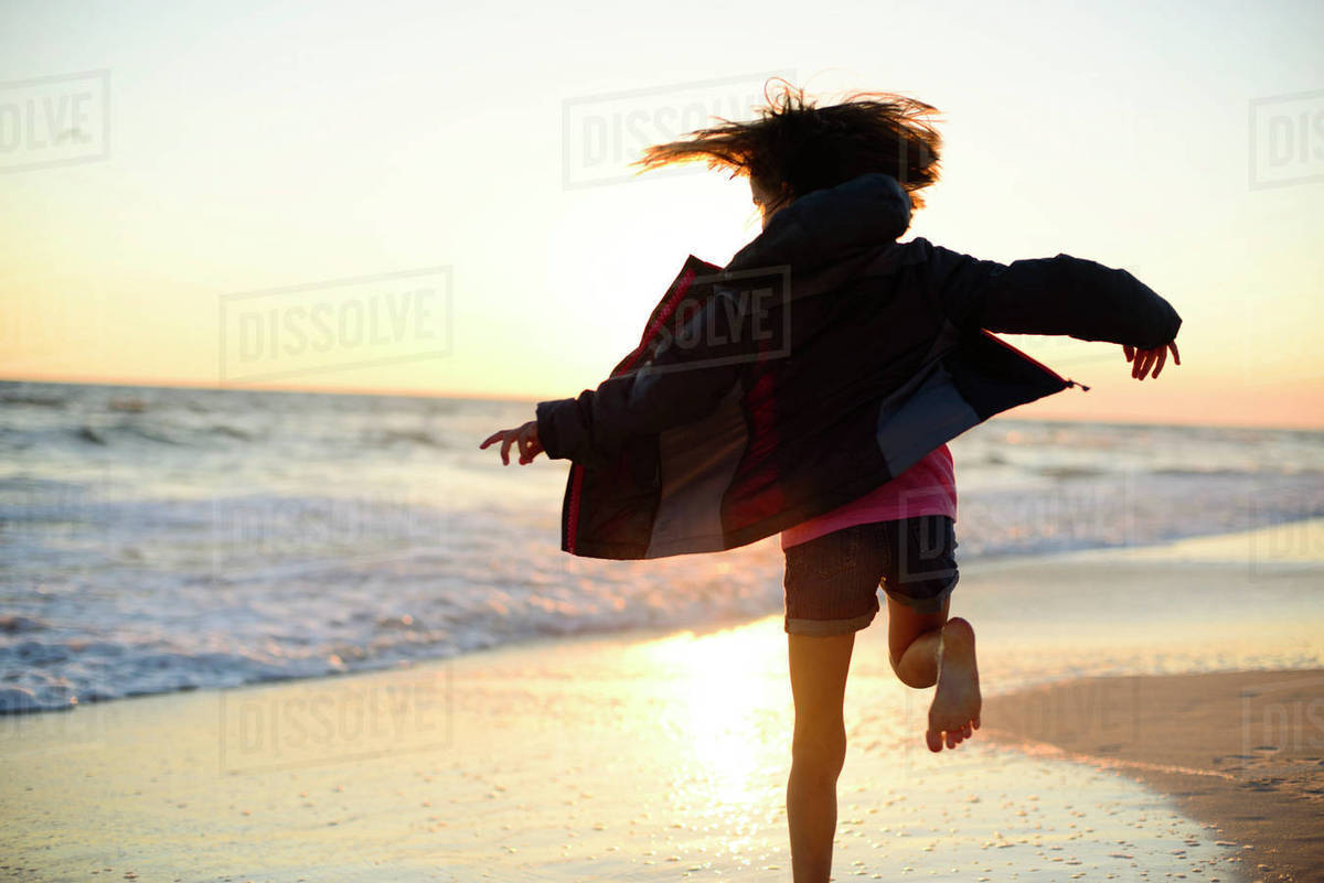 rear view of playful girl running on shore against clear sky during